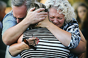 The mother of shooting victim Jake Long, center, is embraced during a community vigil honoring the victims of a shooting that occurred early Saturday morning at a house in Mukilteo, killing three teenagers and wounding one, Sunday, July 31, 2016 at the Mukilteo Church of Jesus Christ of the Latter Day Saints.