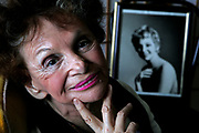 """Elaine Dundy, 80, poses with an old photo of herself in the 1950s, at her home in Los Angeles. Dundy, former wife of Kenneth Tynan, has a flash of success as a novelist in the 1950s with her book """"The Dud Avocado."""" Now, the novel has been re-issued, and the movie is in the works."""