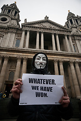 © licensed to London News Pictures. London, UK 18/01/12. A supporter of the Occupy London protesters holds up a sign reading 'whatever. We have Won' in reaction to the High Court Ruling to uphold the City of London's Corportations bid to evict the protesters from land surrounding St Paul's Cathedral. Photo credit: Tolga Akmen/LNP