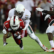 Louisville Cardinals wide receiver DeVante Parker (9) gets tackled during the NCAA Football Russell Athletic Bowl football game between the Louisville Cardinals and the Miami Hurricanes, at the Florida Citrus Bowl on Saturday, December 28, 2013 in Orlando, Florida. Louisville won the game by a score of 36-9. (AP Photo/Alex Menendez)