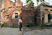 A man walks past a derelict French colonial house in Chandannagar, India