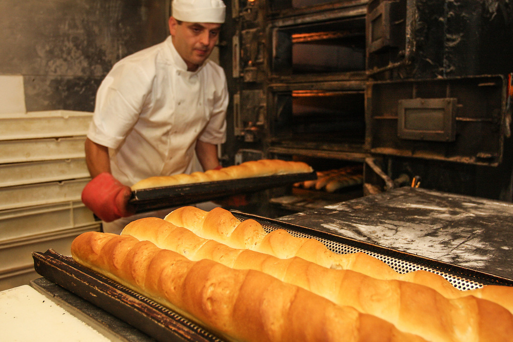 Baker putting bread into traditional ovens. Bakery, London, UK