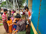 26 OCTOBER 2015 - YANGON, MYANMAR: People clamor to get off and on a Yangon Circular Train in the Da Nyin Station, about 90 minutes from Yangon. The Yangon Circular Railway is the local commuter rail network that serves the Yangon metropolitan area. Operated by Myanmar Railways, the 45.9-kilometre (28.5mi) 39-station loop system connects satellite towns and suburban areas to the city. The railway has about 200 coaches, runs 20 times daily and sells 100,000 to 150,000 tickets daily. The loop, which takes about three hours to complete, is a popular for tourists to see a cross section of life in Yangon. The trains run from 3:45 am to 10:15 pm daily. The cost of a ticket for a distance of 15 miles is ten kyats (~nine US cents), and for over 15 miles is twenty kyats (~18 US cents).    PHOTO BY JACK KURTZ