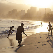 A late afternoon beach scene at Arpoador Beach as locals play football with Ipanema and Leblon in the distance. Rio de Janeiro, Brazil. 8th August 2010. Photo Tim Clayton..