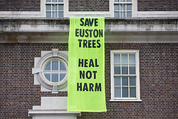 London, UK. 6th February, 2021. A banner reading 'Save Euston Trees - Heal Not Harm' hangs from the Friends House on Euston Road. The banner was hung by environmental activists from anti-HS2 campaign group HS2 Rebellion in solidarity with fellow activists occupying tunnels beneath Euston Square Gardens in order to seek to protect trees from felling in connection with the HS2 high-speed rail project.