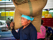 """10 AUGUST 2014 - BANGKOK, THAILAND: A porter carries a sack full of rice into the Poh Teck Tung Shrine in Bangkok. The rice was donated to the shrine for Ghost Month and will eventually be handed out to poor people in the community. The seventh month of the Chinese Lunar calendar is called """"Ghost Month"""" during which ghosts and spirits, including those of the deceased ancestors, come out from the lower realm. It is common for Chinese people to make merit during the month by burning """"hell money"""" and presenting food to the ghosts.     PHOTO BY JACK KURTZ"""