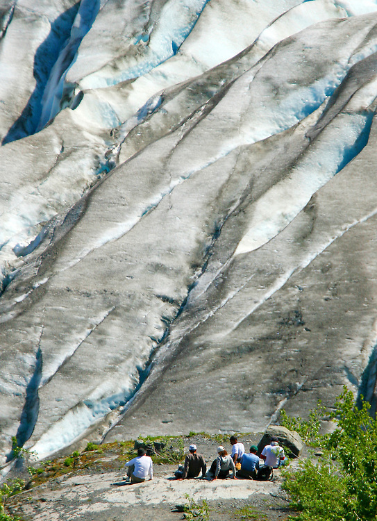 USA, Alaska, Chugach National Forest, Kenai Fjords National Park, a group of hikers rests in view of the lower portion of the Exit Glacier.