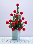 christmas tree with red balls against colored background