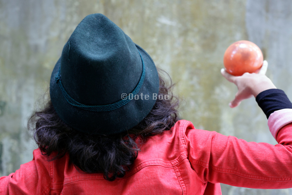 back view of woman playing with a ball
