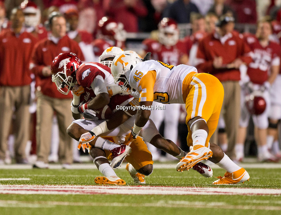 Nov 12, 2011; Fayetteville, AR, USA;  Arkansas Razorbacks wide receiver Jarius Wright (4) is brought down by Tennessee Volunteers linebacker A.J. Johnson (45) and another defender during a game at Donald W. Reynolds Razorback Stadium. Arkansas defeated Tennessee 49-7. Mandatory Credit: Beth Hall-US PRESSWIRE