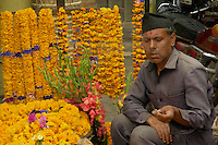 Merchant in Indra Chawk Square in Kathmandu, sells beautiful flower garlands while smoking a cigarette.