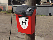 Red bin for dog waste only mounted on wooden post next to pathway in Woodbridge, Suffolk, England, UK