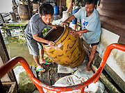 """05 OCTOBER 2015 - BANGKOK, THAILAND: Workers pack a resident's """"khlong jar"""" on moving day in the Wat Kalayanamit neighborhood. Khlong jars are large ceramic jars used to store domestic water in homes that don't have municipal water. The people moving were being evicted from their homes. Fifty-four homes around Wat Kalayanamit, a historic Buddhist temple on the Chao Phraya River in the Thonburi section of Bangkok, are being razed and the residents evicted to make way for new development at the temple. The abbot of the temple said he was evicting the residents, who have lived on the temple grounds for generations, because their homes are unsafe and because he wants to improve the temple grounds. The evictions are a part of a Bangkok trend, especially along the Chao Phraya River and BTS light rail lines. Low income people are being evicted from their long time homes to make way for urban renewal.        PHOTO BY JACK KURTZ"""