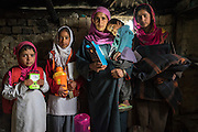 (L-R: Muskaan, 6, Hafiza, 10, Amina, 38, Kheshboo, 3 and Tasfiya, 16.) Amina, stands for a portrait with her children in their collapsed house in Purnishadashah village, Jammu and Kashmir, India, on 24th March 2015. Amina's house was destroyed in the floods forcing her to move in with relatives. Save the Children supported them with kitchen items, hygiene kits, food baskets, blankets, a solar powered lamp and education kits for the children. Photo by Suzanne Lee for Save the Children