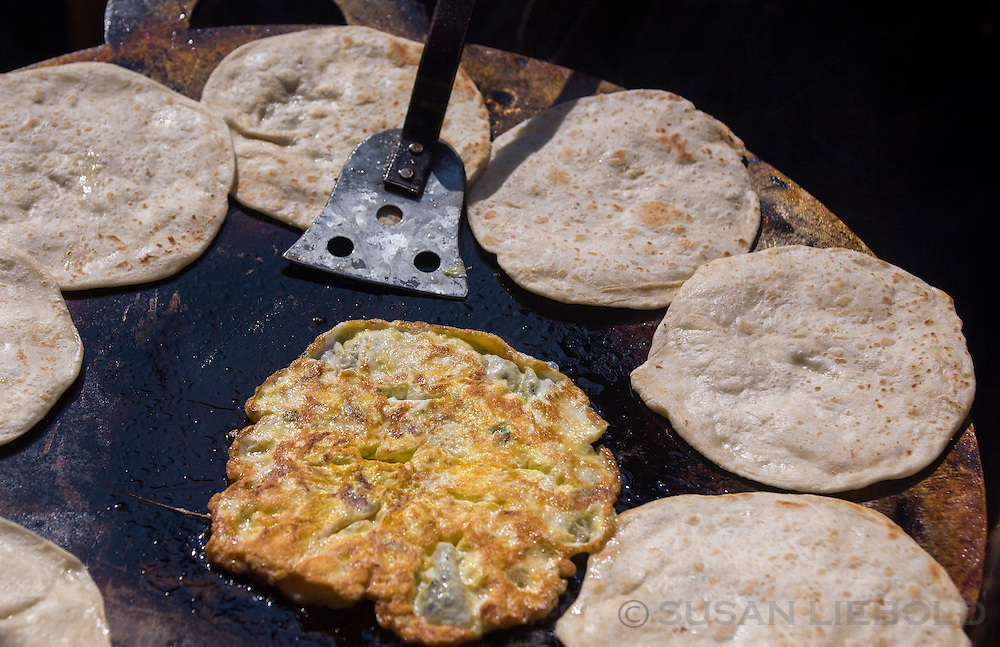 Chapatis and fried eggs being cooked on a grill outside in Dhaka, Bangladesh.