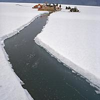 Eclipse Sound, near Bylot Island, Nunavut, Canada.Tourists in an Inuit komatik sled cross a lead in frozen sea ice.