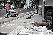 A boy walks along the national highway that surrounds the cemetery Olongapo City in search of water.<br /> The graves come to the roadside.