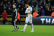 a dejected Swansea city capt Ashley Williams walks off at end of match with his arm held in a sling. Barclays Premier League match, Swansea city v Chelsea at the Liberty Stadium in Swansea, South Wales on Saturday 17th Jan 2015.<br /> pic by Andrew Orchard, Andrew Orchard sports photography.