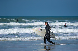 A surfer walks along the beach at Fistral Beach in Newquay, Cornwall.