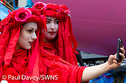 Two performers stop for a selfie ahead of their act as hundreds of environmental protesters from Extinction Rebellion occupy Oxford Circus, a pink yacht being the focal point of their presence, with traffic denied access to two of London's busiest streets. London, April 16 2019.