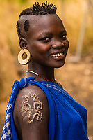 Mursi tribe woman with clay disc in her ear lobe and scarification on her shoulder, Lower Omo Valley, Mago National Park,  Ethiopia.