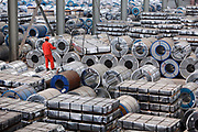 A worker stands on top of stacks of steel products at a warehouse run by the Shanghai Yirong Trading Company Ltd in Shanghai, China on 10 April 2009. China is world's largest steel producer and consumer, its seemingly insatiable appetite for raw material to fuel its economic growth has been the most important reason behind the recent commodities boom and wealth accumulated by western mining companies.