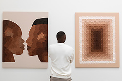 """© Licensed to London News Pictures. 14/10/2021. LONDON, UK. A visitor views (L) """"Soft interior, Strong Exterior"""", 2020, and """"World Peace"""", 2021, both by Hannah Nijsten. Opening day of the eighth edition of START, an art fair presenting contemporary works by over 70 emerging international artists and galleries from over 25 countries.  The show runs to 17 October at Saatchi Gallery in Chelsea.  Photo credit: Stephen Chung/LNP"""