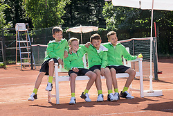 Group of young boys watching match on tennis court, Bavaria, Germany