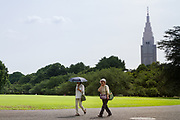Two older Japanese women walk through Shinjuku Gyo-en Park with the NTT Docomo Tower behind. Shinjuku, Tokyo, Japan Tuesday June 26th 2018