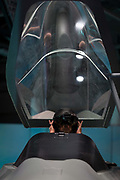 A visitor to the BAE Systems exhibition hall sits in a mock-up of the Tempest fighter, a replacement for the Typhoon, in the companys exhibition hall at the Farnborough Airshow, on 18th July 2018, in Farnborough, England.