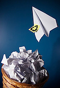 A paper airplane with the recycle symbol drawn onto a small post-it note flies off from a garbage can filled with crumpled sheets of paper. (photo illustration)