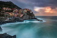 A long exposure view at dawn of the beautiful small fishermen village of Manarola, one of the five villages altogether known as Cinque Terre. Taken about 30 minutes before sunrise on a morning at the end of May, just after a storm with strong winds.