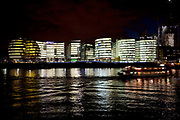 Night scene as a boat passes looking over the River Thames towards the skyline of More London area offices and business district. This area is a recent development which is now thriving and bustling with more buildings being constructed in this moderm glass style and filling the area with office workers.