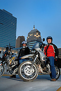 Dual sport motorcycle riders pausing on parking garage with downtown Oklahoma City skyline in background.