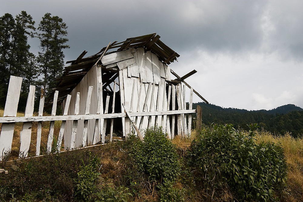A dilapidated wooden outhouse under stormy skies at the entrance to the El Rosario Monarch Butterfly Sanctuary in Michoacan State, Mexico.
