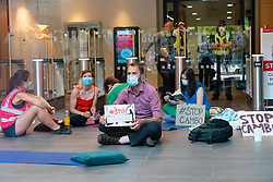Edinburgh, Scotland, UK. 19 July  2021. Protestors opposed to the approval of new Cambo North Sea oil and gas field occupy HM Government Queen Elizabeth house in central Edinburgh today. Protestors are still inside and outside the building in the afternoon under police watch. Protestors cite global warming and climate change as a reason to leave all new oil and gas deposits in the ground undeveloped. Pic; Protestors sitting inside foyer of Queen Elizabeth house . Iain Masterton/Alamy Live news.