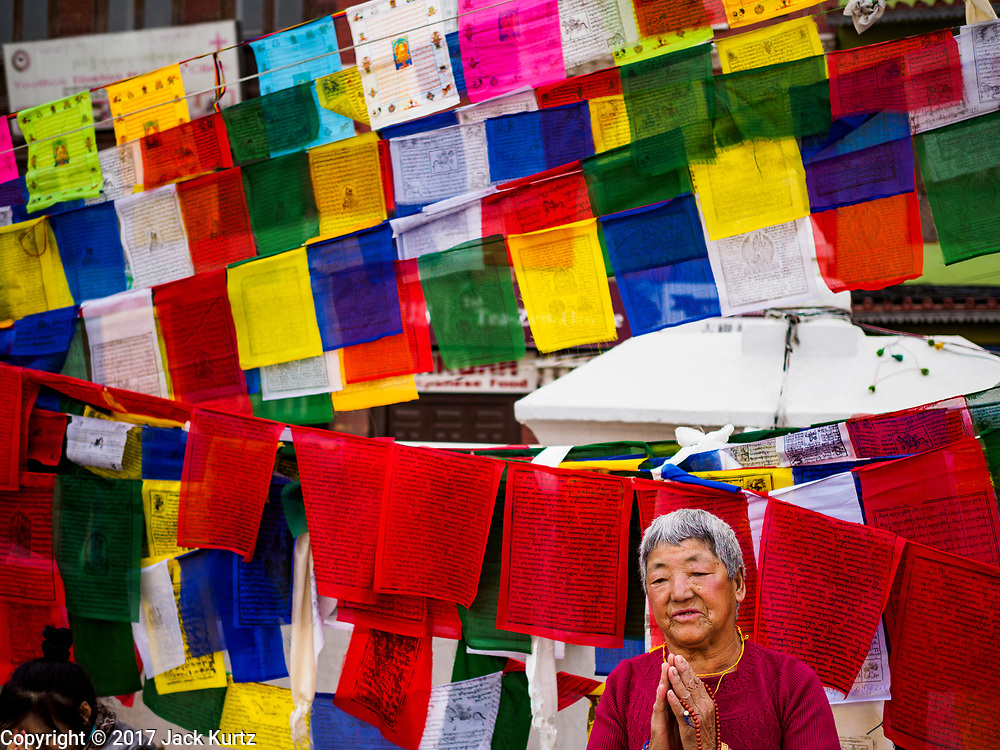 16 MARCH 2017 - KATHMANDU, NEPAL:  A woman prays in front of fluttering prayer flags during morning prayers at Boudhanath Stupa in Kathmandu. The stupa is the holiest site in Nepali Buddhism. It is also the center of the Tibetan exile community in Kathmandu. The Stupa was badly damaged in the 2015 earthquake but was one of the first buildings renovated.      PHOTO BY JACK KURTZ