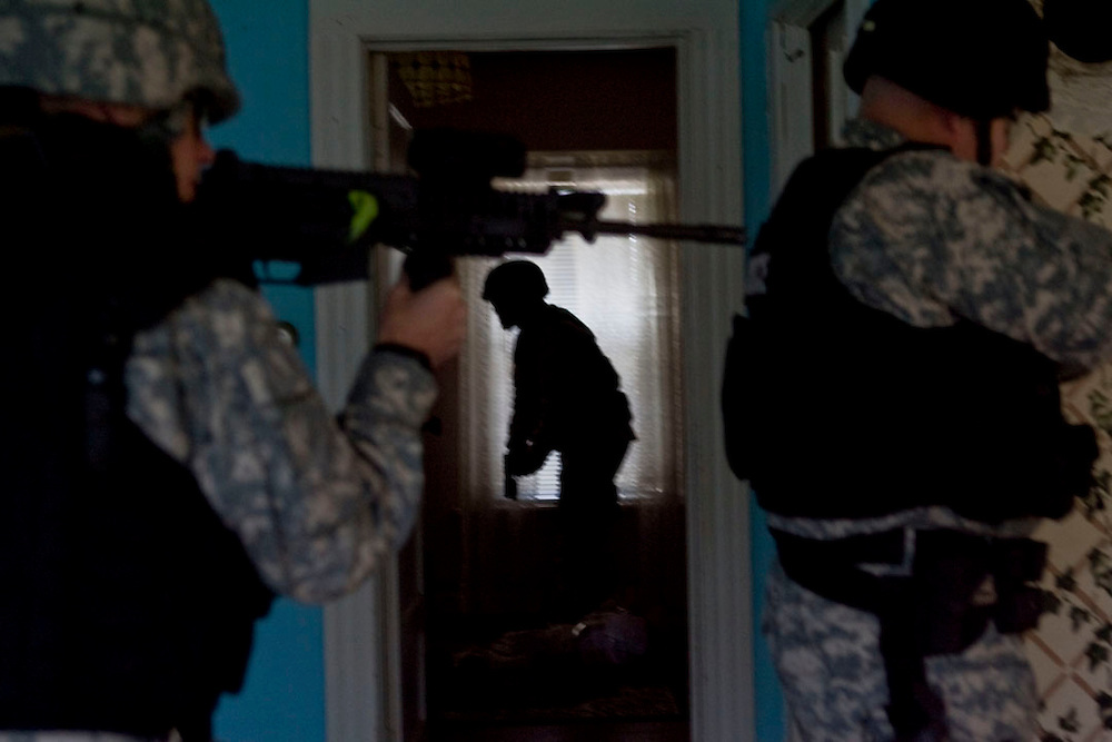 Torrington, Conn. - 21 October 2008 -Torrington Police Officer Tom Rouleau appears between Winsted Police Officer Jay Hermenau, left, and Torrington Police Officer Ken DeLand, right, as they train for covert movement for SWAT team training at an abandoned house...Josalee Thrift Photo