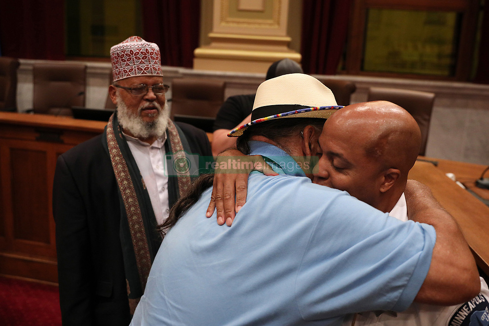 August 9, 2017 - Minneapolis, Minnesota, U.S. - Acting police chief MEDARIA ARRADONDO  got a hug from local activist CLYDE BELLECOURT as IMAM SHEIKH SA'AD MUSSE ROBLE looked on following the public hearing. The Minneapolis City Council's Public Safety, Civil Rights and Emergency Management Committee held a public hearing on the nomination of Arradondo to be the City's next police chief Wednesday, at City Hall. (Credit Image: © Anthony Souffle/TNS via ZUMA Wire)