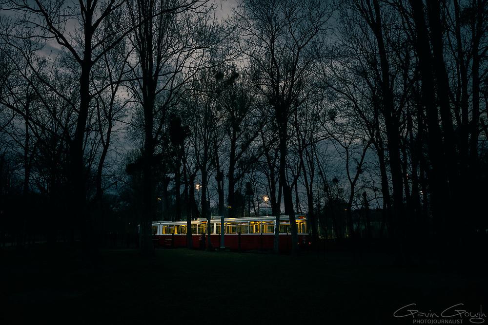Number 1 tram with the interior illuminated arriving at Prater Hauptallee terminus station, Prater Park, Vienna, Austria