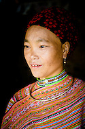 Vietnam, Bac Ha. Portrait of a Flower Hmong woman wearing a beautiful traditional dress.