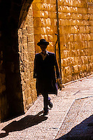 A Hassidic Jew walking down a street in the Old City, Jerusalem, Israel.