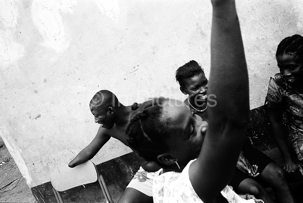 James and his wife Nbalu, sit and chat with their neighbours. Amputee and war Wounded resettlement camp, Hastings, Sierra Leone, 2004<br /> Rebel forces, the Revolutionary United Front in Sierra Leone, systematically murdered, mutilated, and raped civilians during the country's civil war as a policy of terror