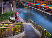 """The San Antonio River Walk (also known as Paseo del Río) is a network of walkways along the banks of the San Antonio River, one story beneath the streets of Downtown San Antonio, Texas, USA. Lined by bars, shops and restaurants, the River Walk is an important part of the city's urban fabric and a tourist attraction in its own right.<br /> Today, the River Walk is an enormously successful special-case pedestrian street, one level down from the automobile street. The River Walk winds and loops under bridges as two parallel sidewalks lined with restaurants and shops, connecting the major tourist draws from the Alamo to Rivercenter Mall, to the Arneson River Theatre, to Marriage Island, to La Villita, to HemisFair Park, to the Tower Life Building, to the San Antonio Museum of Art, and the Pearl Brewery. During the annual springtime Fiesta San Antonio, the River Parade features flowery floats that """"float"""" down the river."""