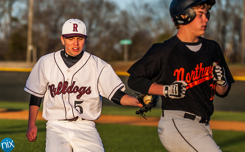 A Northwest Cabarrus runner scores as Robinson's Tyler Kocher tries to make it to the plate Tuesday night at Jay M. Robinson High School. The Trojans won the game 14-2 after five innings of play.