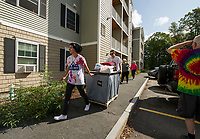 Raymond Townsend and Samuel Avard help Sarah Simpson with her mother Molly Simpson at the Apple Ridge student apartments during Move In day at Lakes Region Community College Sunday morning.  (Karen Bobotas/for the Laconia Daily Sun)