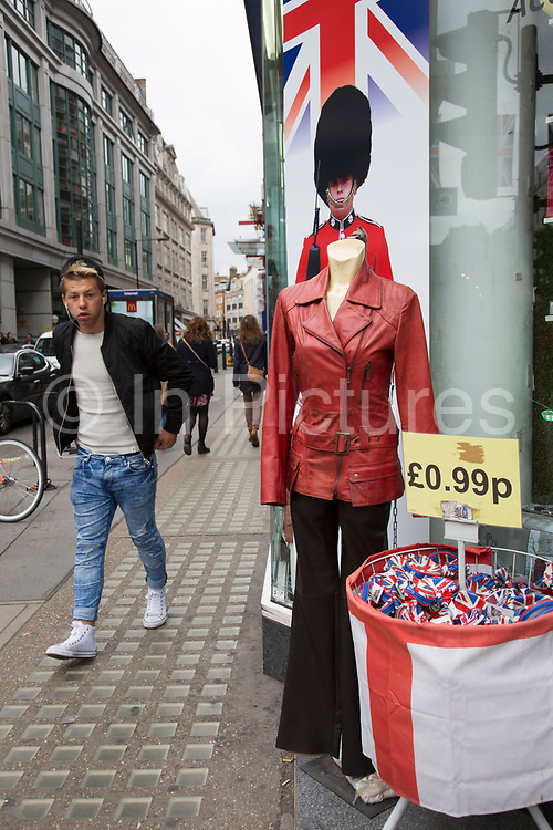 Red leather jacket blending in with a cut out picture of a military Guard complete with bear skin head dress in London, England, United Kingdom.