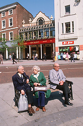 Group of elderly people sitting on park bench in city centre,