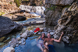 A vacationing couple from California taking in the good life in Wyoming.   For thousands of years, Wyoming's natural hot springs have been revered attractions and used by American Indian tribes, mountain men, early pioneers and settlers who found a welcoming oasis in the healing waters of the mineral springs. Granite Hot Springs, Bridger Teton National Forest high in the Gros Ventre Mountains.