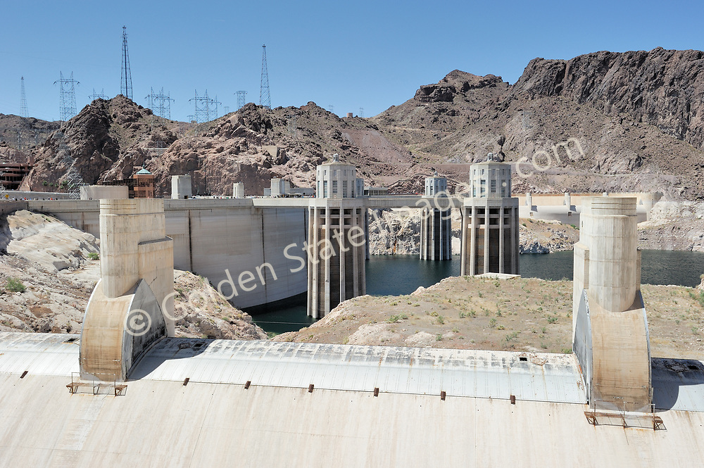 Hoover Dam intake towers and spillway.<br /> <br /> Hoover Dam is designed to never have the water level of Lake Mead overtop the dam. There are spillways on each side which route excess storage around the dam.